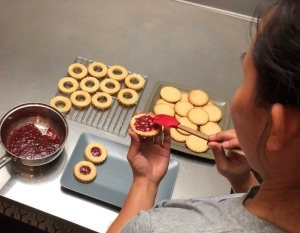Woman spreading strawberry jam on a biscuit
