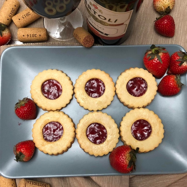 Blue plate with six Jammie Dodgers, surrounded by strawberries, corks and wine.