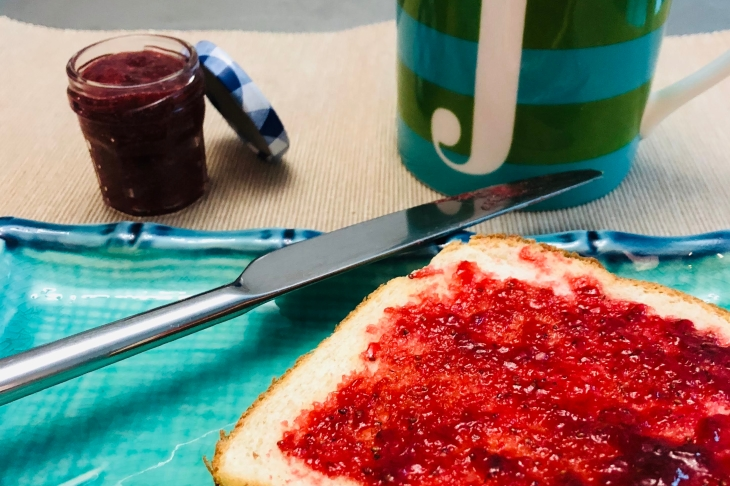 Toast with strawberry jam on a blue plate.