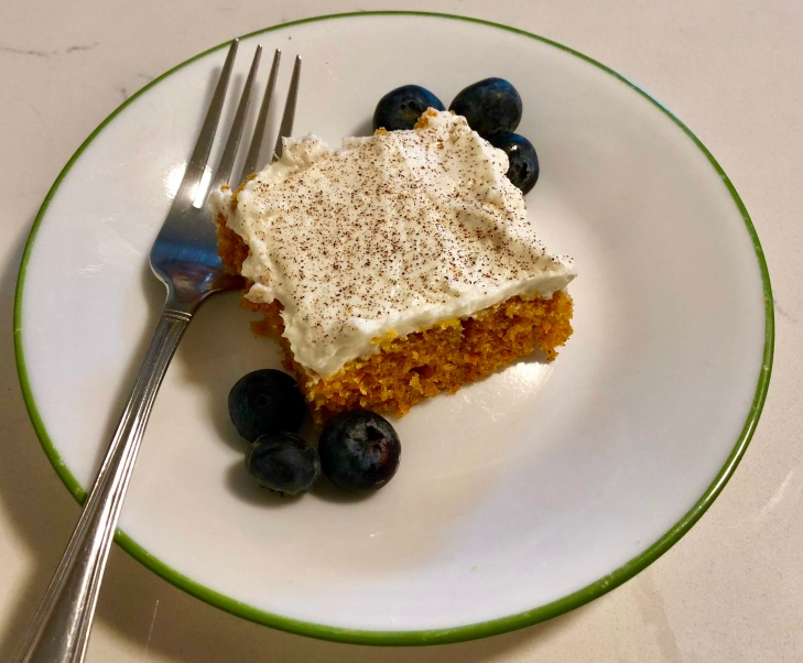 Slice of frosted carrot cake with fresh blueberries