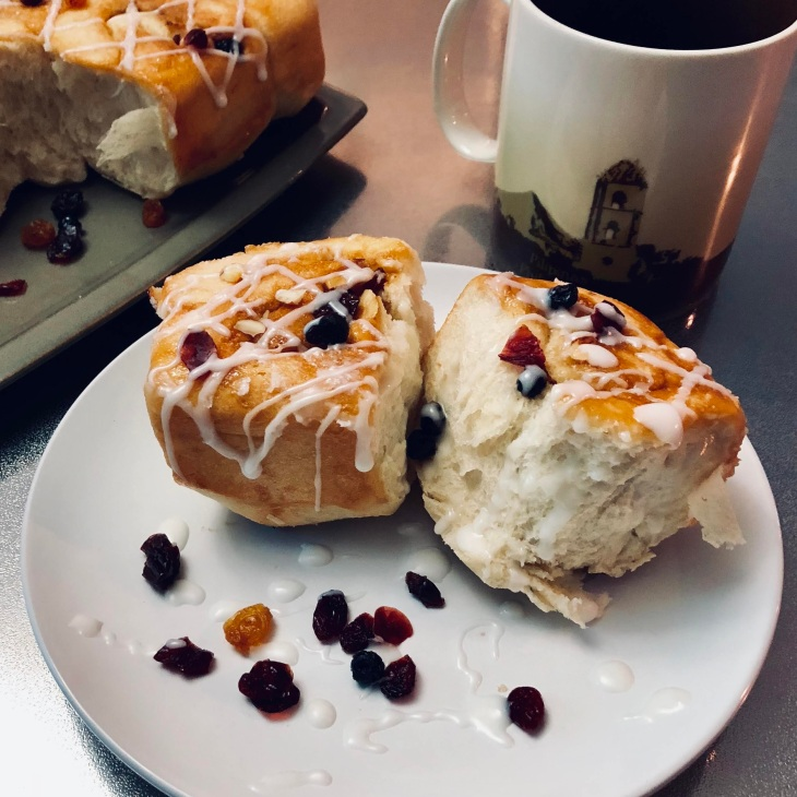 Pulled apart Chelsea buns on a plate with coffee