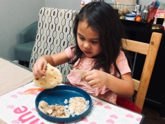 girl tearing up naan