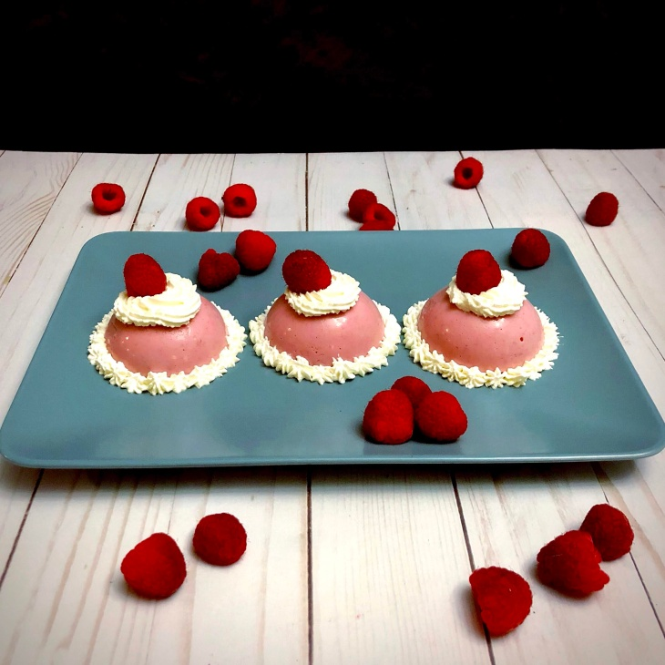 three raspberry blancmange on a plate